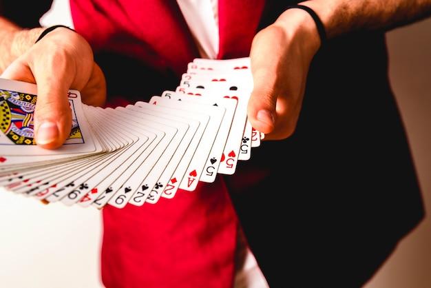 Hände des magiers, die tricks mit einem kartenspiel machen.