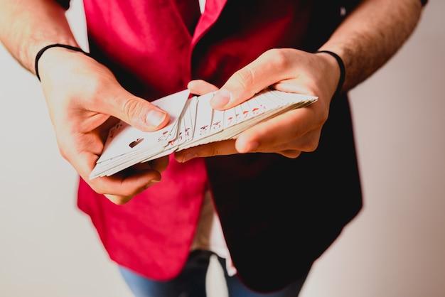 Hände des magiers tricks mit einem kartenstapel tuend.