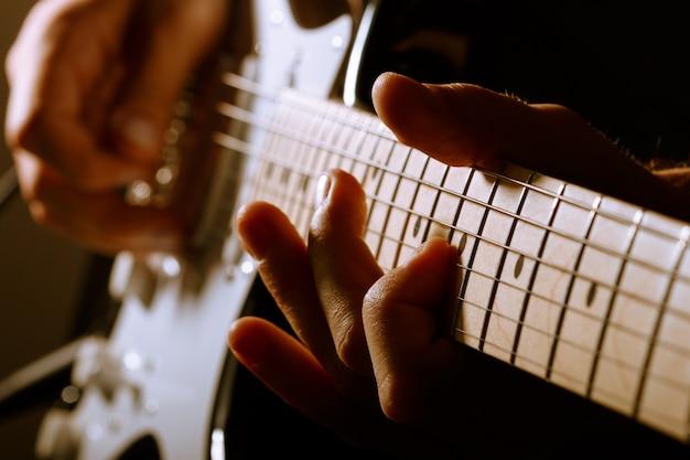 Hände des mannes, der e-gitarre spielt