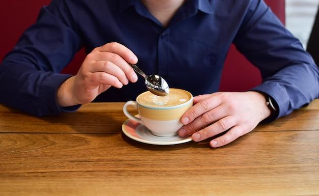 Hände des mannes, der eine kaffeetasse cappuccino auf einem tisch in der cafeteria hält.