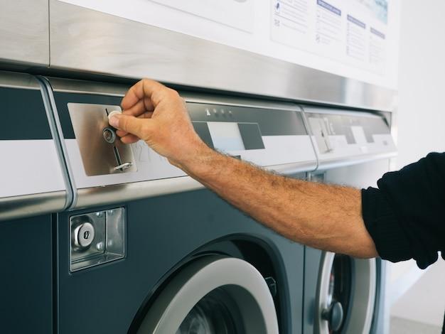 Hände des mannes, der münzen für die waschmaschine im waschsalon auswählt. reinigungskonzept