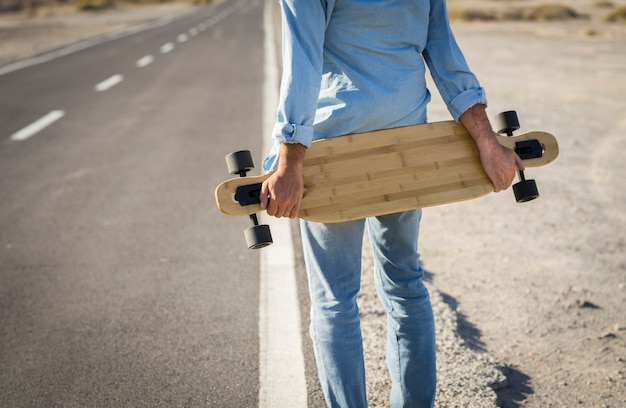 Hände des mannes, der skateboard auf der straße hält rückansicht des mannes, der denim-kleidung trägt und skateboard auf der landstraße hält. sportler, der skateboard hält und am straßenrand wartet