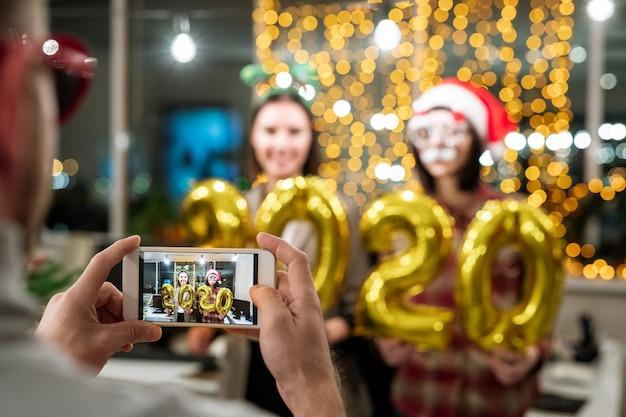 Hände des mannes, der smartphone mit zwei jungen glücklichen geschäftsfrauen mit aufblasbaren zahlen auf seinem bildschirm hält, während foto von ihnen macht
