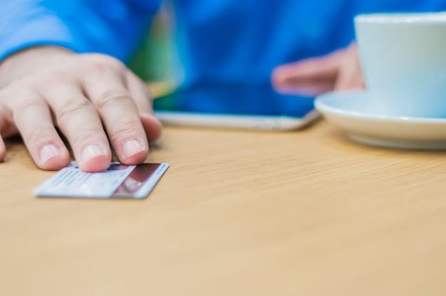 Hände des mannes geben plastikkarte zum kellner, um für den auftrag zu zahlen. geschäftsmann bezahlt mit einer kredit- oder debitkarte