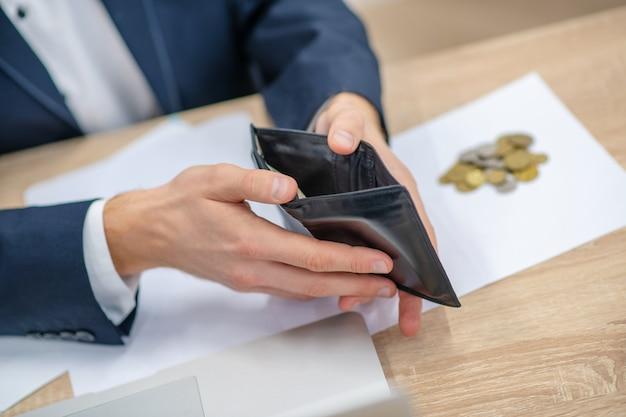 Hände des mannes im geschäftsanzug mit offener brieftasche über tisch neben kleinen münzen