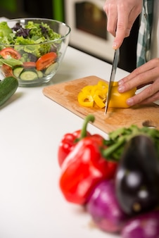 Hände des mannes kocht gemüsesalat in der küche.
