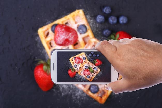 Hände des mannes mit dem smartphone, der foto selbst gemachte traditionelle belgische waffeln macht