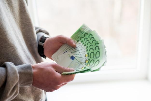 Hände des mannes mit euro auf weißem hintergrund.