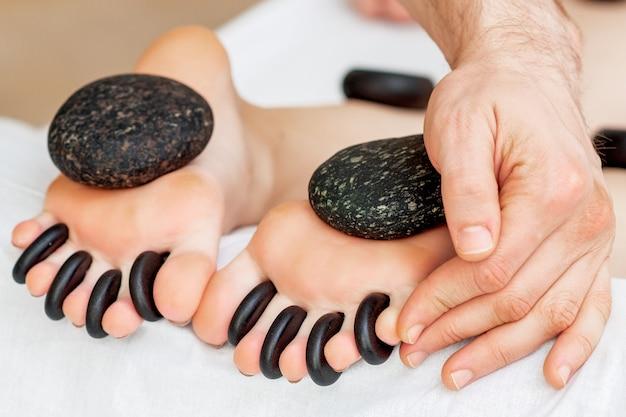 Hände des massagetherapeuten legen steine zwischen die zehen der frau, während die steinmassage an den füßen erfolgt