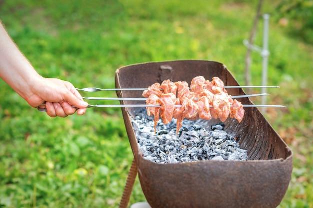 Hände des menschen bereitet grillfleisch zu
