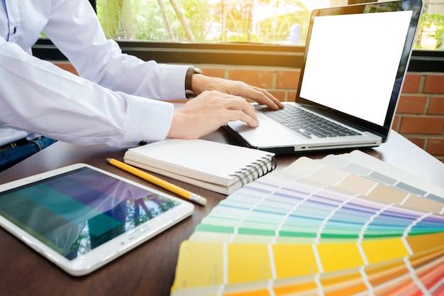 Hände des modernen grafikdesigners des männlichen hippies im büro, das mit farbproben arbeitet