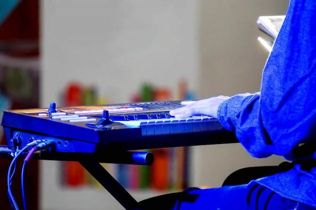 Hände des musikers eine elektronische tastatur auf stadium mit blauer beleuchtung spielend