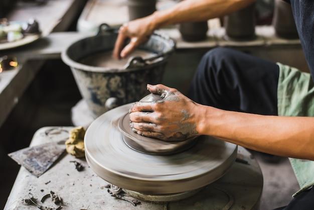 Hände des nahaufnahmetöpfers, die weichen lehm formen, um einen tönernen topf zu machen
