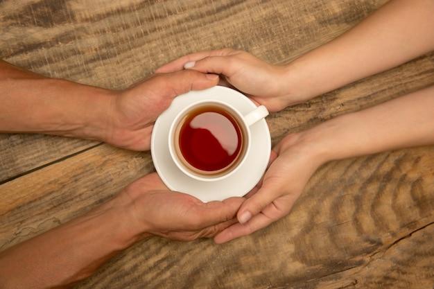 Hände des paares, das tasse tee, draufsicht auf hölzernem hintergrund mit exemplar hält. getränke, wohnkomfort, warmer event und abend, gemütlichkeit mit der familie. exemplar für werbung.