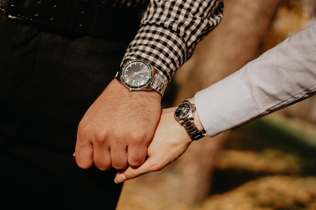 Hände des paares. paar liebhaber, die händchen halten. zeiger mit armbanduhr und ring