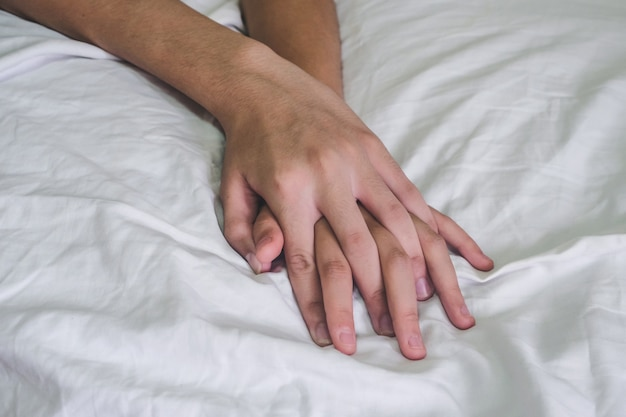 Hände des paarliebhaberssex auf dem bett, konzept über liebe, sex und lebensstil.