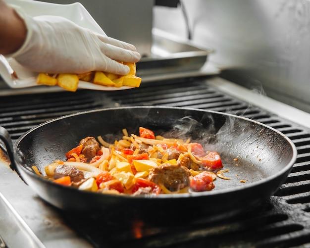 Hände des restaurantkochs, die fleisch mit gemüse in einer pfanne kochen