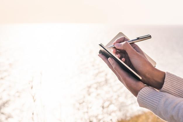 Hände des schreibens der jungen frau in einem notizblock vor dem meer