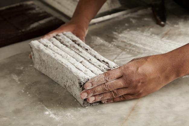 Hände des schwarzen mannes chef hält frisch gebackene schokoriegel in zuckerpulver vor dem verpacken, nahaufnahme in professioneller handwerklicher süßwaren