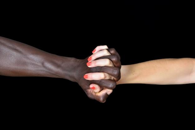 Hände des schwarzen mannes und der weißen frau auf schwarzem hintergrund
