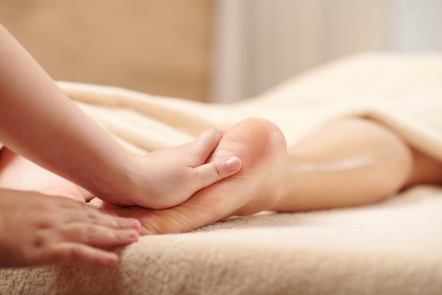 Hände des therapeuten massieren die füße der jungen frau mit feuchtigkeitsspendenden ölen