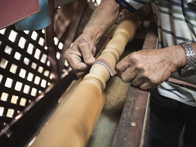 Hände des tischlers holz auf drehbank drehend