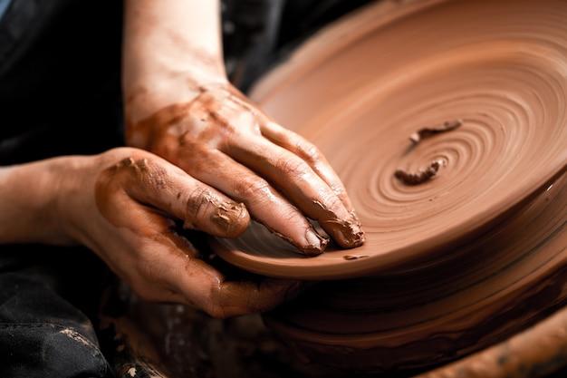 Hände des töpfers, der tontopf macht, nahaufnahmefoto