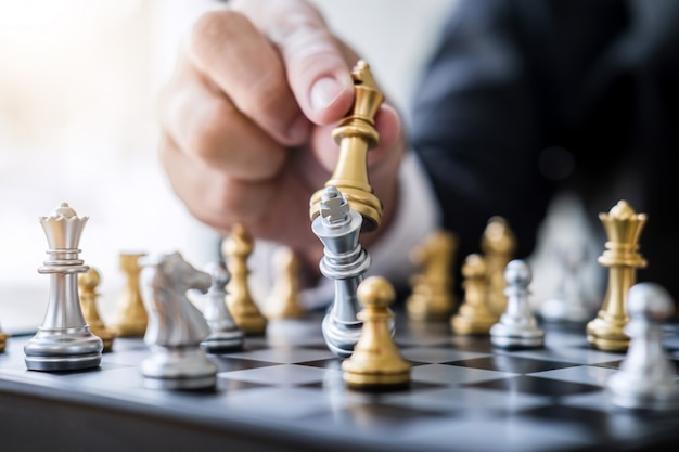 Hände des überzeugten geschäftsmannes schachspiel zum neuen strategieplan der entwicklungsanalyse spielend