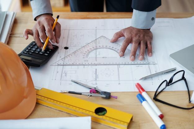 Hände des unerkennbaren männlichen architekten, der an technischer zeichnung arbeitet und taschenrechner verwendet