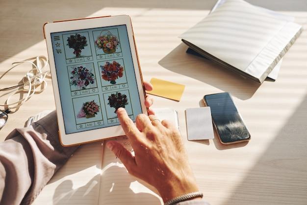 Hände des unerkennbaren mannes blumenblumenstrauß online auf tablette vorwählend
