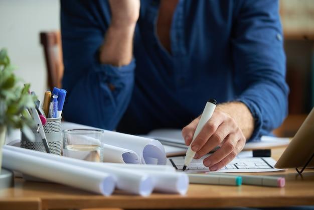 Hände des unerkennbaren mannes sitzend am schreibtisch im büro und auf grundriss mit markierung zeichnend