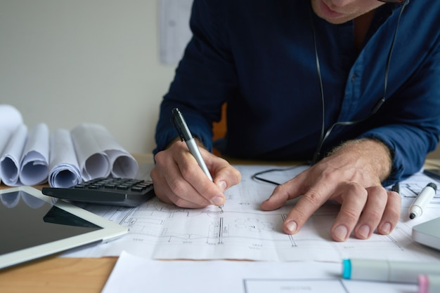 Hände des unerkennbaren mannes zeichnend auf technischen plan im büro