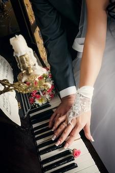 Hände des verheirateten mannes und der frau mit den eheringen, die fast auf schlüssel des klaviers mit beige rosen legen