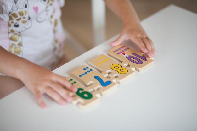 Hände des vorschulkindkindes, das lernspiele mit holz spielt