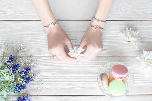 Hände des weiblichen floristen, der blumen für das erstellen des blumenstraußes auf weißem holztisch hält, flache lage. draufsicht auf arbeitsplatz der jungen kreativen frau mit süßigkeiten. schule für floristik