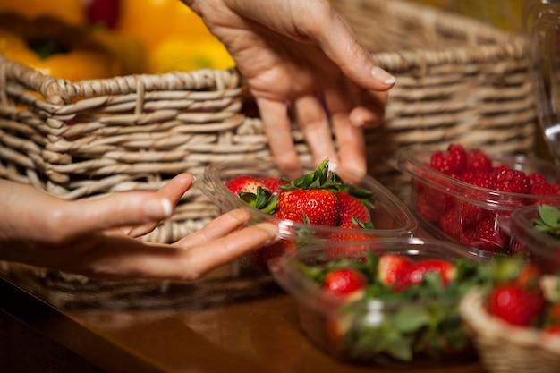Hände des weiblichen personals, das schüssel erdbeeren hält