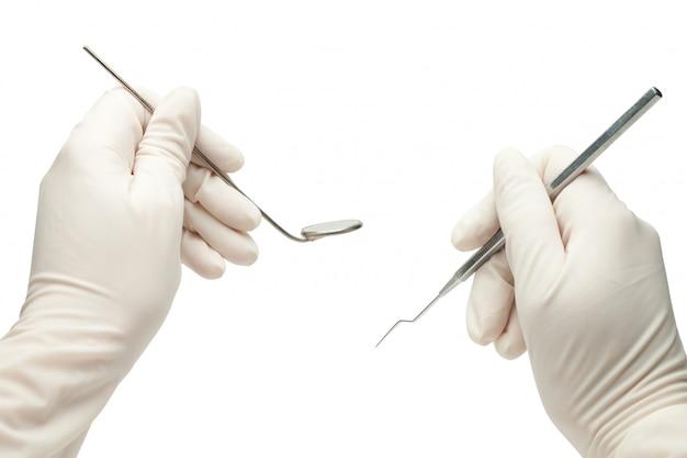 Hände des zahnarztes, der seine werkzeuge während der patientenuntersuchung hält