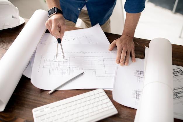 Hände des zeitgenössischen architekten mit teilern, die skizze des hochbaus auf einem der papiere durch arbeitsplatz machen