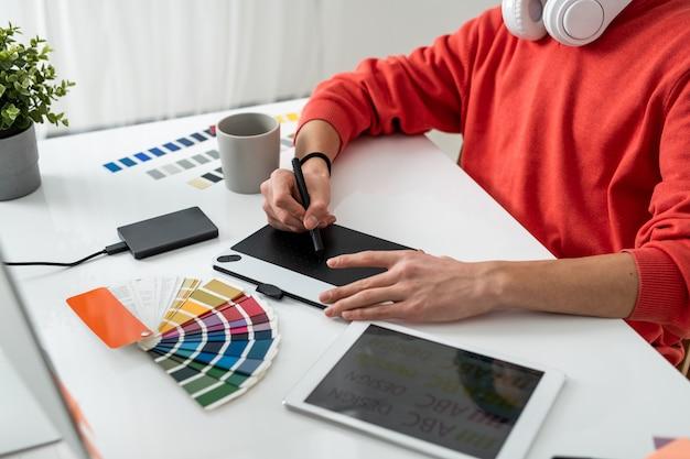 Hände des zeitgenössischen freiberuflichen designers mit stift über grafiktablett, das fotos durch schreibtisch retuschiert