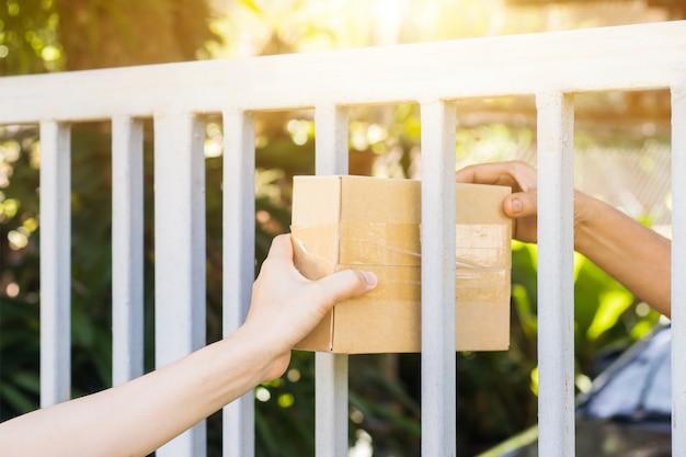 Hände des zustellers oder postboten tragen das warenpaket und werden zu hause an den empfänger geschickt