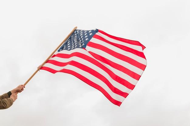Hände, die amerikanische flagge winken