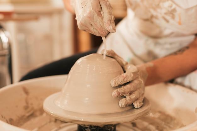 Hände, die an töpferscheibe arbeiten