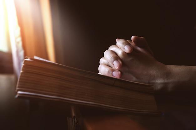Hände, die auf bibel neben einem fenster-licht beten