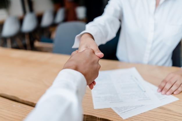 Hände, die auf einem geschäftsabkommen im büro rütteln