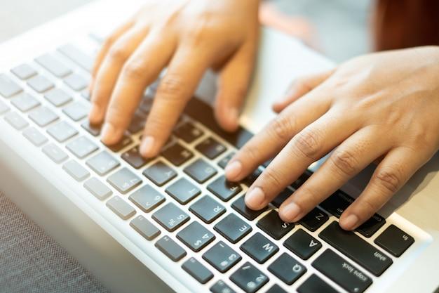 Hände, die auf einer notizbuchtastatur schreiben. selektiver, weicher fokus