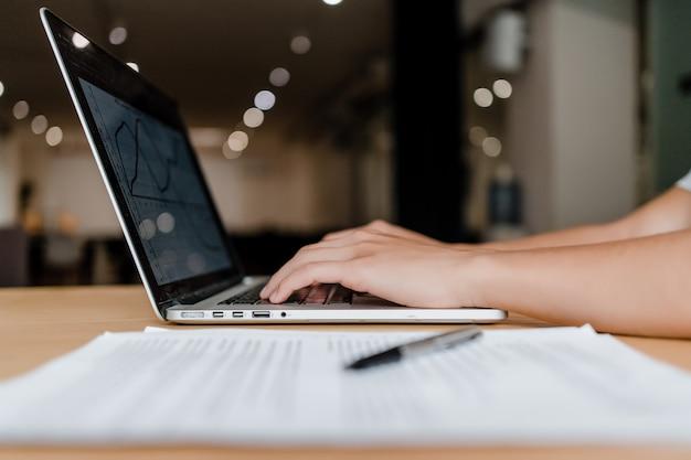 Hände, die auf laptoptastatur im büro schreiben