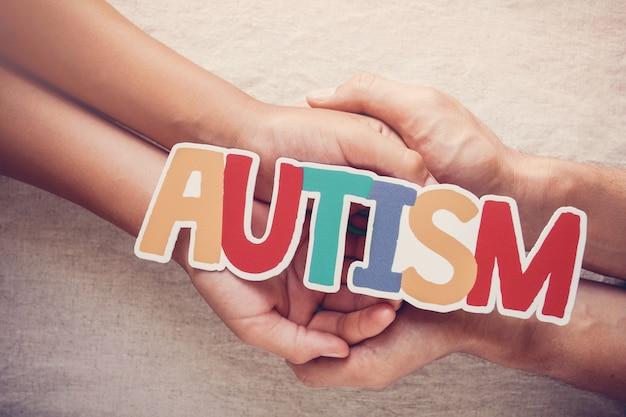 Hände, die autismuswort, konzept der psychischen gesundheit, weltautismus-bewusstseins-tag halten
