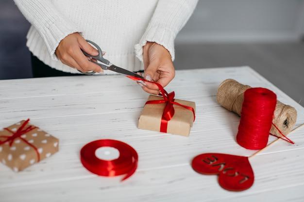 Hände, die band beim verpacken des geschenks schneiden