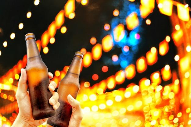 Hände, die bierflaschen und glückliche genießende erntezeit zum klirren von gläsern zusammenhalten.