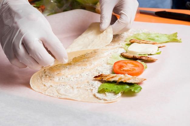 Hände, die burrito vorbereiten
